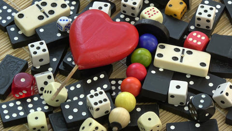 Rotating bones, domino, black and white dices and toys with red heart symbol Filmmaterial