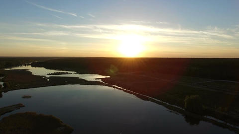 4k Aerial - Drone flying over forest lake at sunset Footage
