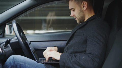 Attractive smiling man typing laptop computer while sitting inside his car Footage