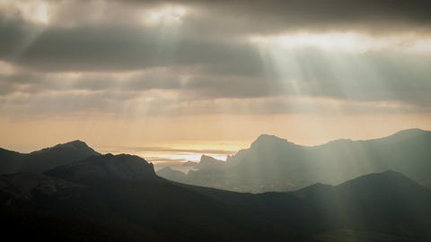 Sun rays through the clouds floating over the mountains and the sea. Timelapse Footage