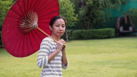 Asian girl with red oriental style umbrella on green nature background Live Action