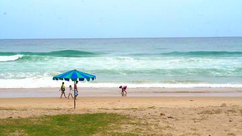 PHUKET ISLAND, THAILAND - July 2015: Phuket beach high wave with tourist walking Footage