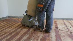 Floor sanding. Sanding machine is removing old oil-color paint Live Action
