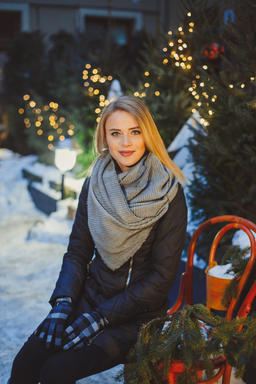 Young Blonde caucasian woman in black coat and gray scarf sitting on the bench Photo