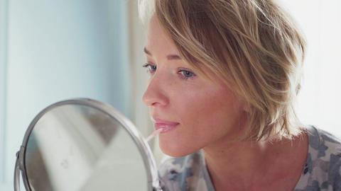 Adult woman makes makeup applying lipstick Live Action
