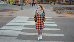 Fashionable Lady in a Plaided Coat is Crossing the Road and Looking Around Footage