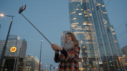 Young Woman Makes Selfie at the Background of Night Modern City Center Footage