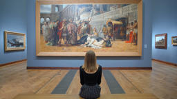 Young Woman Sitting on a Bench in the Art Gallery and Looking at a Huge Picture Footage