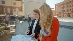 Two Young Tourists Ladies are Loughing while Exploring Paper Map of new City Footage