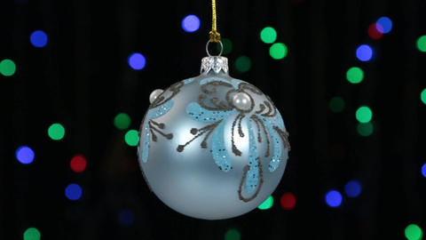 Close-up, the rotation of a blue Christmas ball hanged on a golden rope Live Action