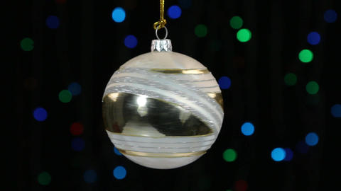 Close-up, the rotation of a white Christmas ball hanged on a golden rope Footage