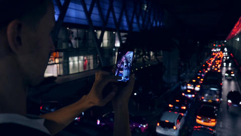 Young Hipster Tourist Takes Smartphone Picture in Night Bangkok City Car Traffic Footage