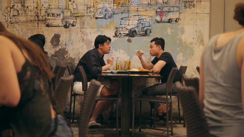 Male Couple Talking and Enjoying Dinner in Chinese Restaurant in China Town Footage