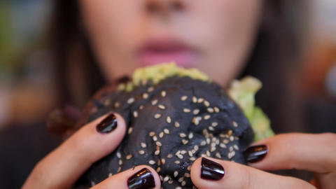 Young Caucasian Woman Enjoys Eating And Tasting Delicious Vegetarian Burger 4K Footage