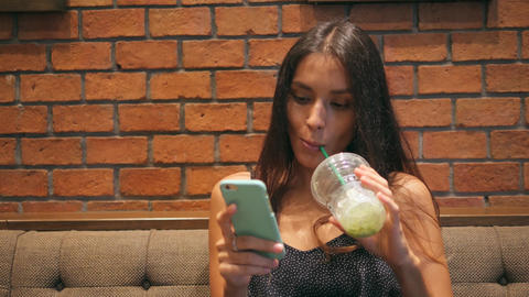 Young Attractive Girl Drinking Matcha Green tea and Texting on Cellphone in the Footage