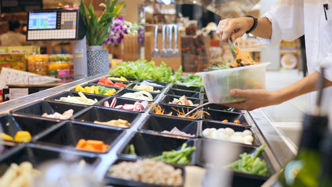 Salad Bar in Shopping Mall. Young Woman Buying Organic Vegetables for Salad Live Action