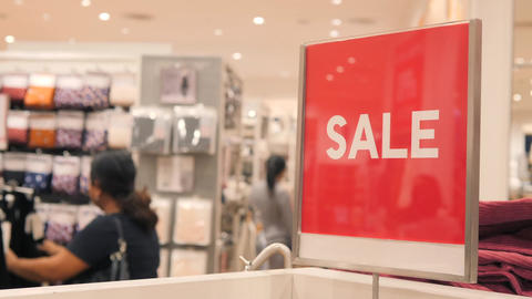 Red Sale Sign in Crowded Clothing Store. Christmas Promotion in Shopping Mall Footage