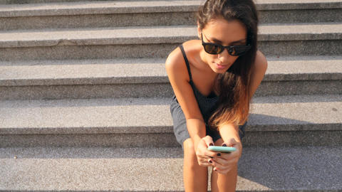 Attractive Mixed Race Student Girl Typing Text on Mobile Phone Sitting on Old Archivo