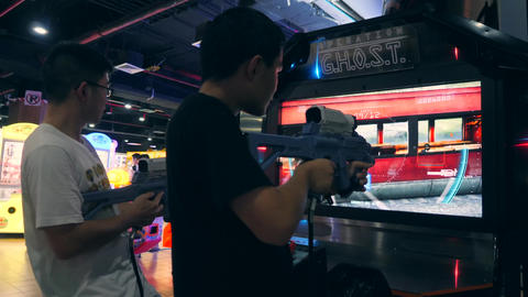 Young Mixed Race Friends Playing Arcade Shooter Game Machine in Game Zone MBK Footage