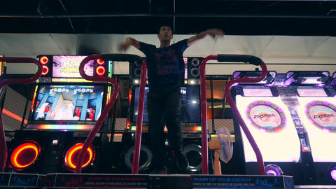 Asian Man Playing Dance Revolution Game and Dancing on Arcade Machine Pad in Footage
