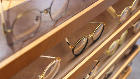 Woman Choosing Glasses at Shelf Display in Shopping Mall. 4K, Slow Motion Footage