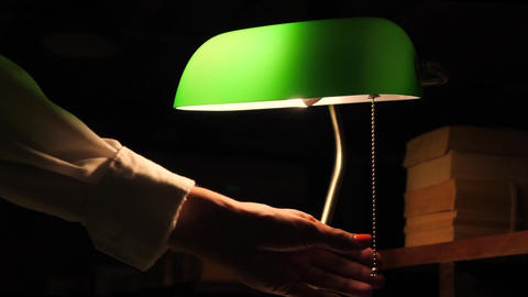 Female Hand Turned Off Green Table Lamp in Library. 4K Footage