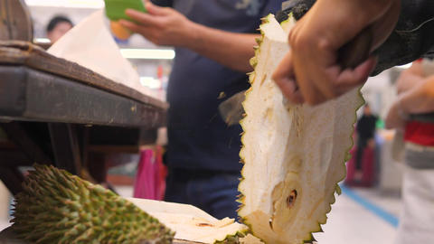 Fruit Seller at Night Market Cutting Exotic Durian Montong. 4K. Bangkok Footage