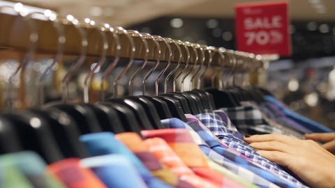 Female Hands Running on Hangers with Colorful Mens Shirts. Young Woman Looking Footage