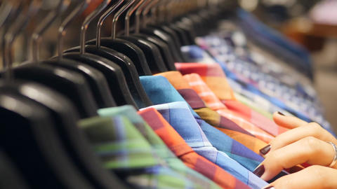 Womans Hands Running on Hangers with Colorful Mens Shirts. Young Girl Looking Footage