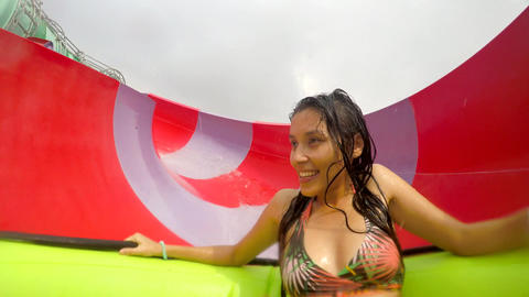 Young Mixed Race Girl Having Fun Water Slide in Waterpark. 4K. Thailand Footage