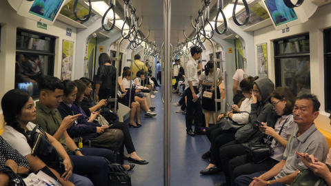 Asian People Using Smart Phones and Gadgets Inside BTS Subway Train Wagon. 4K Footage