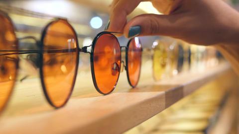 Female Customer Hand Choosing Sunglasses with Orange Lenses from Shelf Display Footage