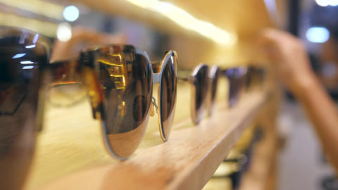 Female Customer Hand Choosing Sunglasses with Brown Lenses from Shelf Display in Footage