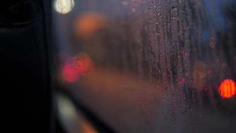 Rain Drops on Bus Window Glass with Blurred Night City Car Lights Bokeh as Footage
