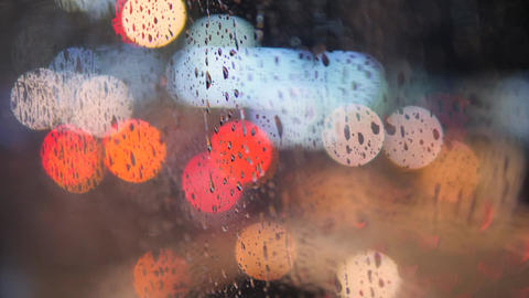 Rain Drops on Car Window Glass with Blurred Night City Car Lights Bokeh as Live Action