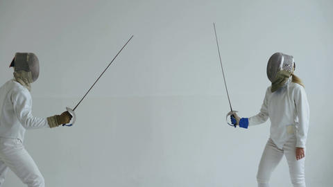 Two fencers have fencing match on white background indoors Footage