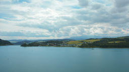 Bewitching Horizontal Panorama of Lake, Mountains, Village, Sky and Clouds Footage