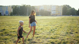 Mother is Playing Ball with the Little Child on Grass at Nice Sunset Archivo