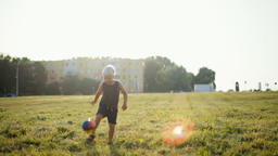 Little Boy is Kicking the Ball on Grass with Beautiful Lense Flare at Sunset Footage