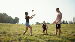 Happy Young Family is Playing Ball with the Little Boy on Grass at Nice Sunset Footage