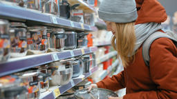 Young Lady is Choosing a Crock Pot in the Houseware Department in Shopping Mall Footage