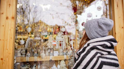 Woman is Walking to a Store with Christmas Decorations during Xmas and New Year Footage
