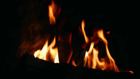 Logs burning in dark room in open fireplace in slow motion 96fps. Closeup on Footage