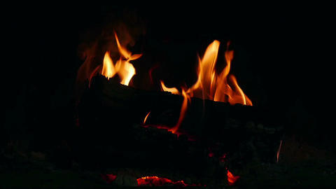 Logs burning in dark room in open fireplace in slow motion. Logs burning in Footage