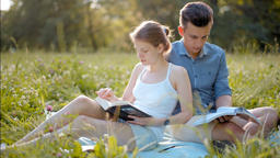 Young Beautiful Couple Reading Books Outdoors in Summer at Picnic with Sun Light 영상물