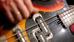 CloseUp of Musician Hands Playing Fast Music with Bass Guitar at the Concert Footage