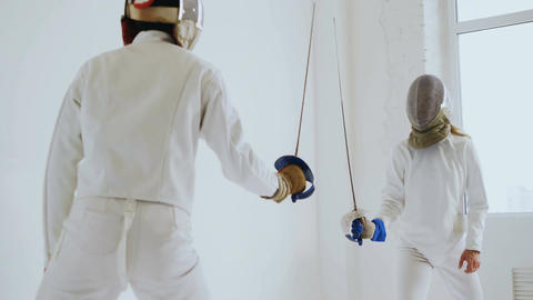 Pair of fencers having practice defence exercises in fencing in studio indoors Footage
