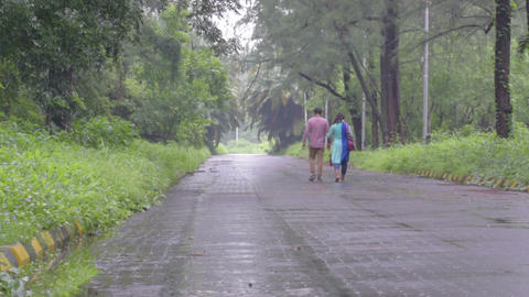 Lovers walking down a road in rain Live Action