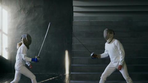 Slowmotion of Two fencers man and woman have fencing match indoors Archivo