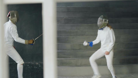 Two fencers man and woman have fencing competition indoors ビデオ